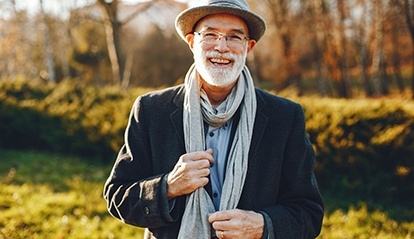Bearded man with hat and scarf smiling outside
