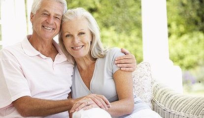 Older couple sitting and smiling with dentures