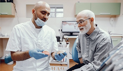 Dentist talking to patient about dentures