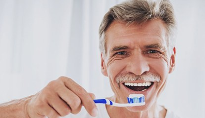 older man brushing his dental implants in St. Albans