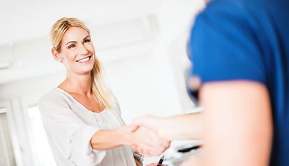 Woman shaking hands with dental team member