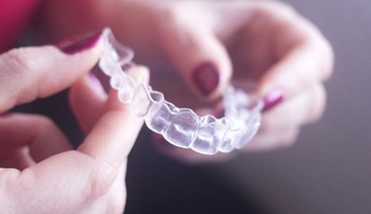 A person holding a clear aligner