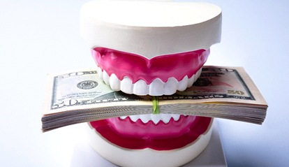 A mouth mold holding a stack of money between the teeth