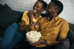 couple sitting on couch and eating popcorn