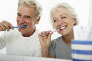 elderly couple brushing their teeth to prevent oral health problems