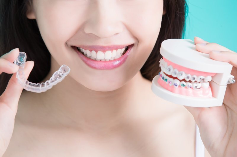 girl holding up Invisalign and braces
